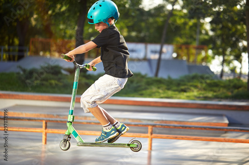 Fototapeta A boy on a scooter and in protective helmet do incredible stunts in skate park