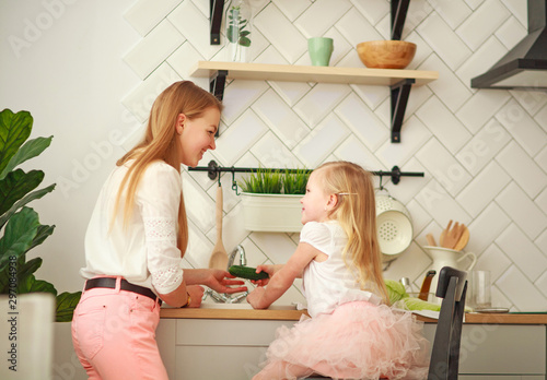 Photo  Happy young mother with daughter in kitchen wash vegetables in sink, interaction
