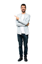 Full-length Shot Of Handsome Man With Beard Pointing To The Side To Present A Product Over Isolated White Background