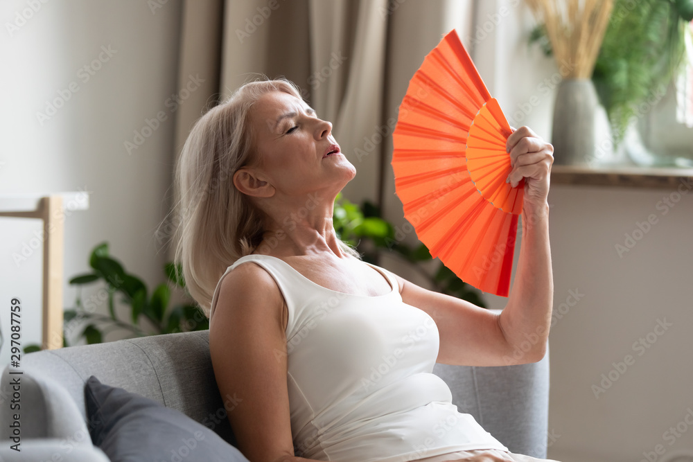 Fototapeta Stressed old woman waving fan suffer from overheating at home
