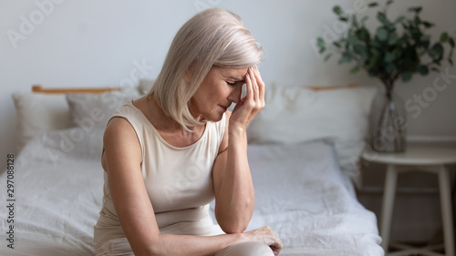 Fotografia  Older woman sit on bed coping with morning headache concept