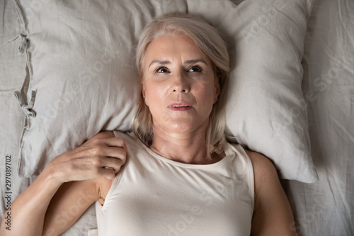 Fotografía  Middle aged woman insomniac lying awake in bed, top view