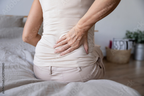 Photo Old mature woman sit on bed touch back feel backpain