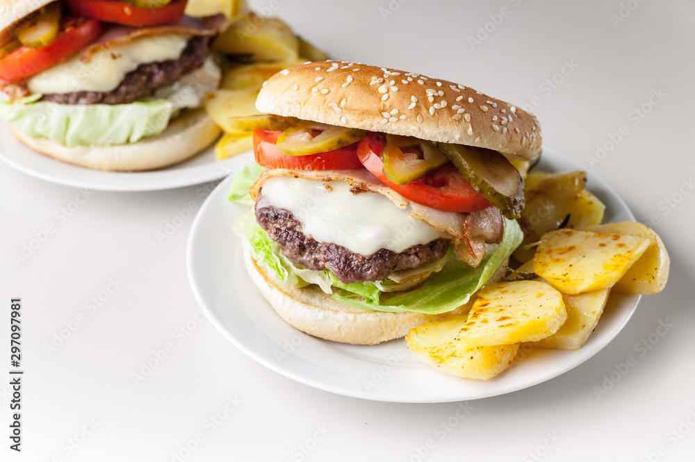 Fototapety, obrazy: Two homemade hamburgers with a juicy meat cutlet, parmesan cheese, green salad, tomatoes and fried potatoes on a light background. Horizontal shot