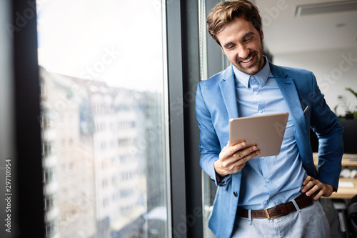 Portrait of businessman smiling while using digital tablet Poster Mural XXL