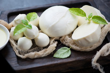 Close-up Of Various Types Of Mozzarella Cheese With Fresh Green Basil On A Black Wooden Serving Tray