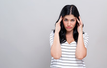 Young Woman Suffering From Headache On A Gray Background