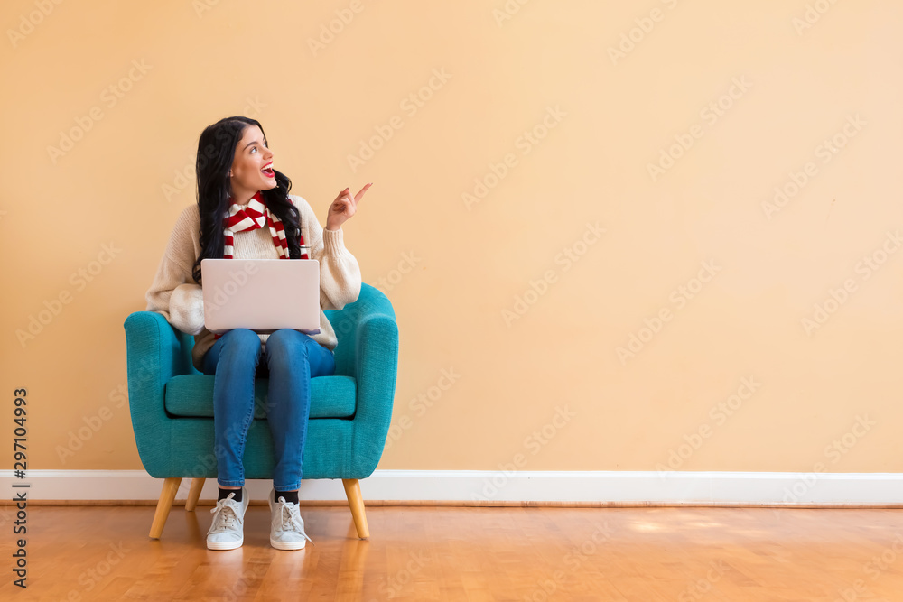 Fototapety, obrazy: Young woman with a laptop computer in a thoughtful pose sitting in a chair