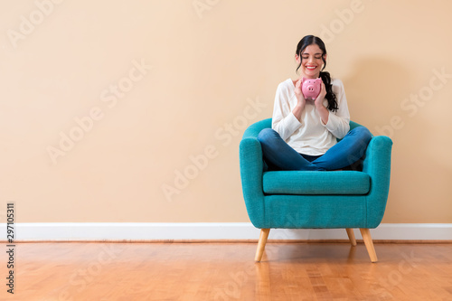 Fotografie, Tablou  Young woman with a piggy bank sitting in a chair