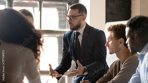 Pinturas sobre lienzo  Serious businessman mentor speaking to diverse people at group training
