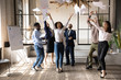 Funny happy multiracial corporate team people dancing toss papers