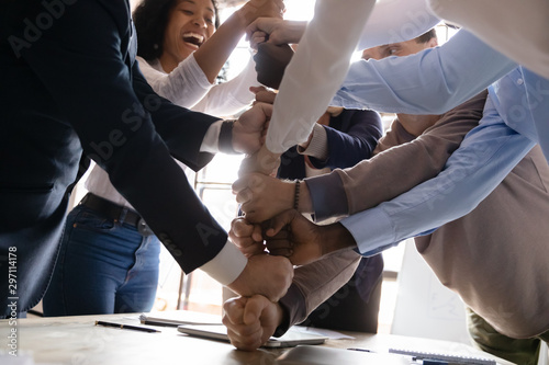 Fototapeta  Overjoyed multiracial business team stack fists together, close up view
