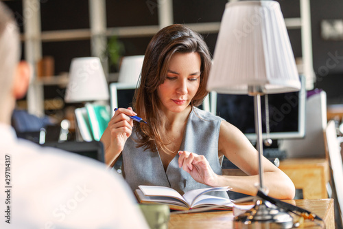 a young woman is working in an office and is going to write something in her notebook on the desktop Canvas Print