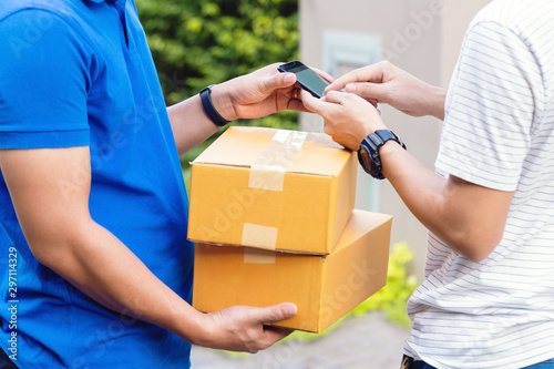 Photo Man receiving package from delivery man appending signature in digital mobile phone after receiving parcel from courier at home