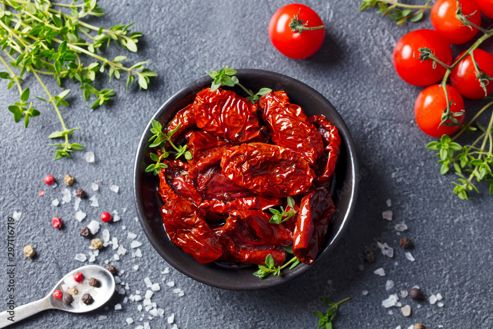 Fototapeta Sun dried tomatoes with fresh herbs and spices. Slate background. Top view.