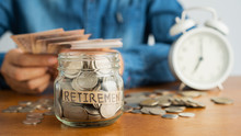 Coin In A Glass Bottle Image Blurred Background  Of Business People Sitting  Counting Money And A Retro White Alarm Clock, Retirement, Finance And Saving Money For Future Concept.