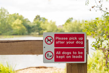 Isolated View Of A New Dog Fouling Sign Seen Attached To A Wooden Entrance To A Public Lake And Nature Area. Installed Due To An Increase In Dog Fouling.