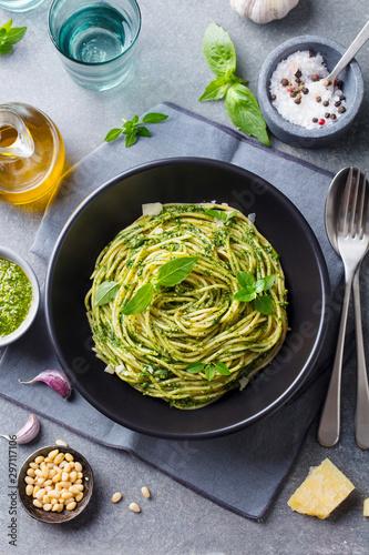 Fotografie, Obraz  Pasta spaghetti with pesto sauce and fresh basil leaves in black bowl