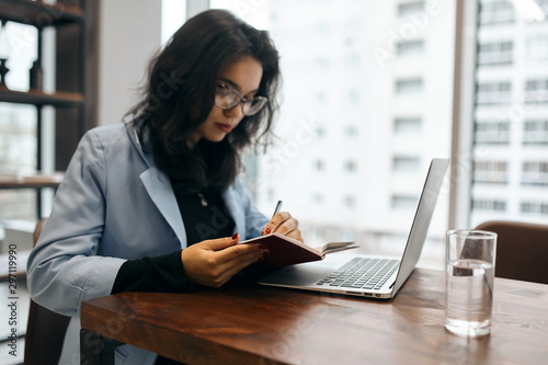 Fotografía  attractive cute office worker writing something on her notepad while sitting at the table in the office with panorama window