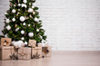 canvas print picture - decorated christmas tree and gift boxes over white brick wall with copy space