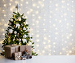 Leinwanddruck Bild christmas and new year concept - beige gift boxes near decorated christmas tree and copy space over white brick wall