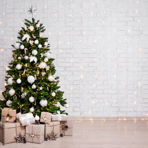 decorated christmas tree, heap of gift boxes and copy space over white brick wall