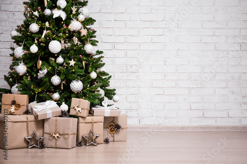Fototapeta decorated christmas tree and gift boxes over white brick wall with copy space