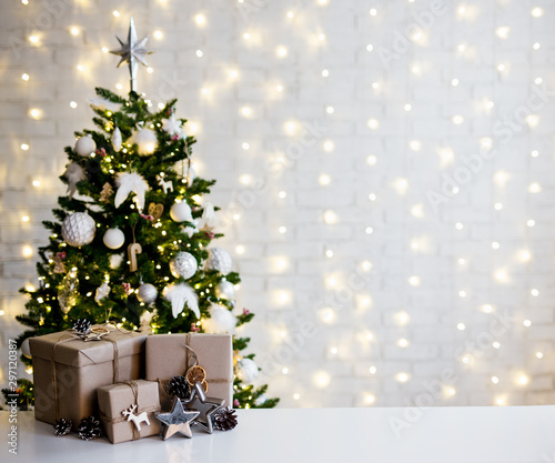 Fototapeta christmas and new year concept - beige gift boxes near decorated christmas tree and copy space over white brick wall obraz