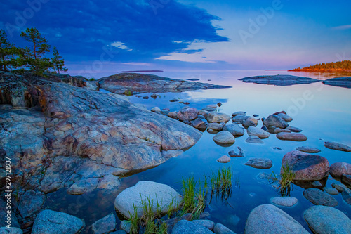 Karelia. Rocky Islands in lake Ladoga. Skerries of lake Ladoga. Northern nature. The island in the distance is illuminated by the setting sun. Evening in Karelia. Travel to Russia.