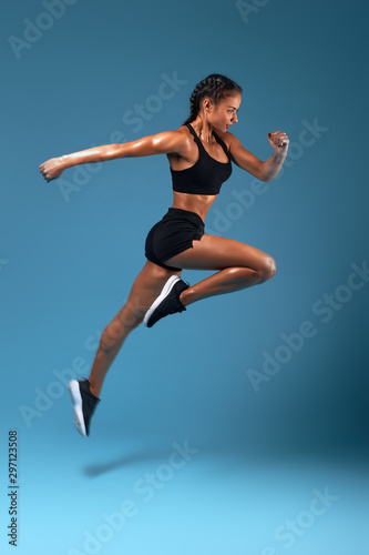 professional athlete training at sport center, full length side view photo. isolated blue background, studio shot.health and body care, wellness, woman is running to her dream