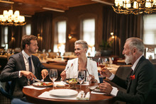 Good Joyful Friends Sit At Round Wooden Table In Cozy Soft Chairs In Bright Lighted Restaurant, Drink Alcohol, Eat Tasty Food, Smile Happily, Posing Over Large Windows With Thick Curtains
