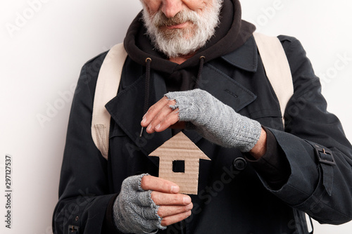 Fotomural unrecognizable old man wearing street clothes holding house made of cardboard, dream about shelter