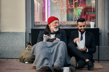 Smiling Rich And Poor Men Together Sitting On Street And Eat While Speaking. Happy Despite Social Inequality