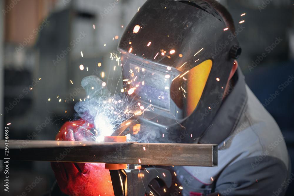 Fototapeta Welder is welding a metal frame.