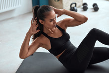Caucasian Fit Female Pump Press In Gym On Mat. Fitness Girl In Black Sportswear Exercising, Hands At Head