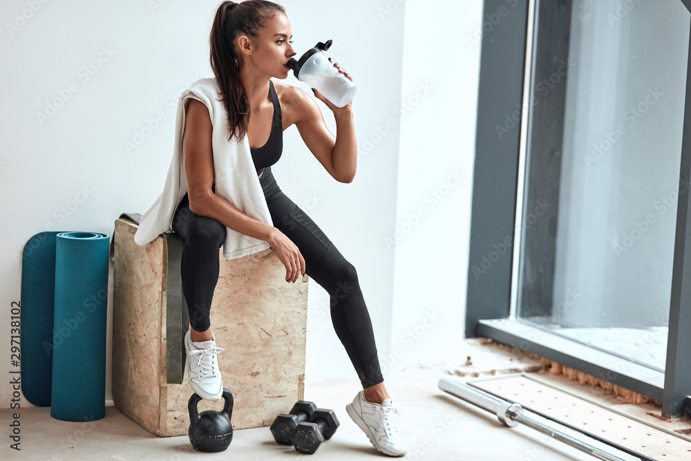 Obraz Young woman in leggins with towel on shoulders drinking water after fitness training fototapeta, plakat