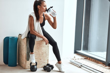 Young Woman In Leggins With Towel On Shoulders Drinking Water After Fitness Training