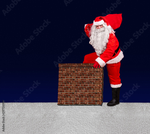 Santa Claus with sack of Christmas gifts stepping into a chimney on snowy roof Canvas Print