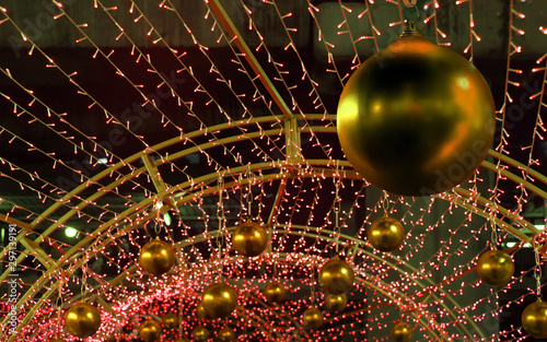 The Colorful Xmas decoration of many LED light. Decorative Christmas golden balls hang out on the outdoor decoration of the construction.