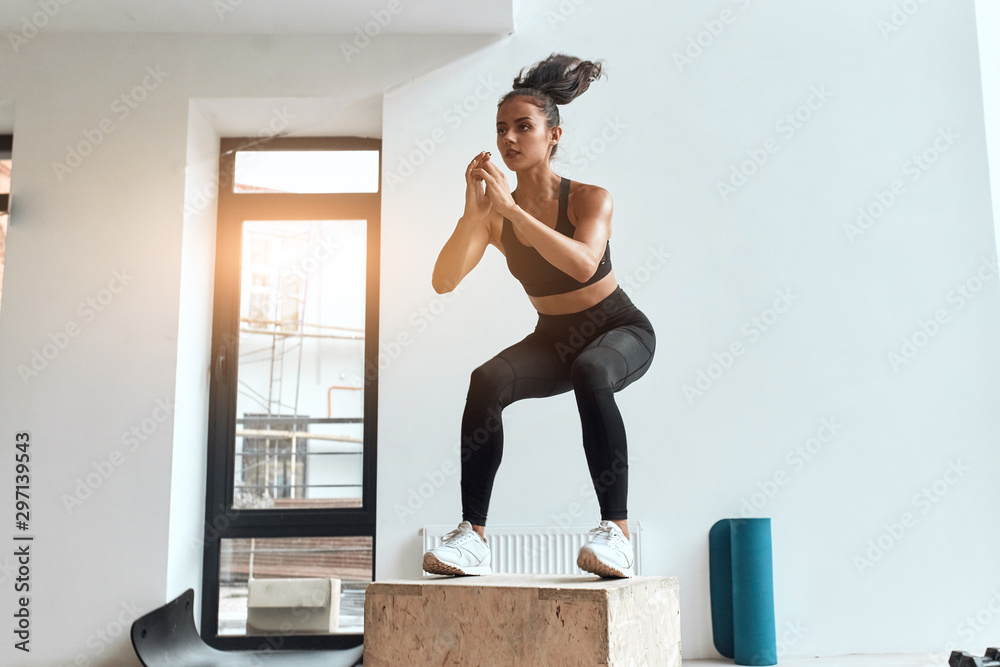 Fototapety, obrazy: Beautiful sporty woman in sportswear jumping on wooden box in gym. Training, cross fit, sport