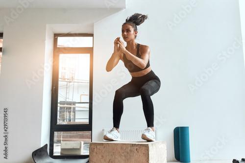 Fotografia  Beautiful sporty woman in sportswear jumping on wooden box in gym