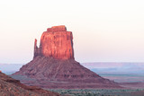 Mittens butte mesa formation with red purple pink rock color in Monument Valley canyons during sunset sunlight in Arizona