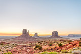 Wide angle view of buttes and horizon in Monument Valley at sunrise colorful light in Arizona with orange rocks