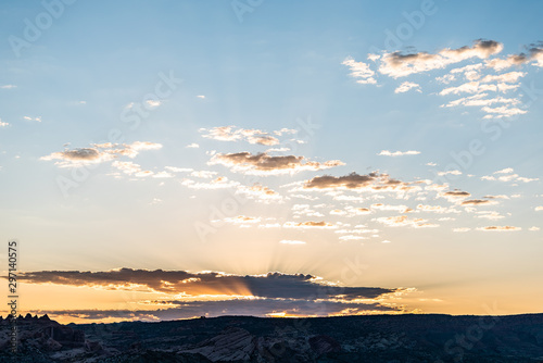 Skyscape colorful view of sunrise with sun behind clouds and sunlight rays beams through sky with horizon valley in Arches National Park, Utah, USA