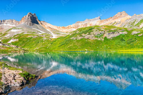 Landscape view of turquoise vibrant Ice lake near Silverton, Colorado on summit rocky mountain peak and snow in August 2019 summer