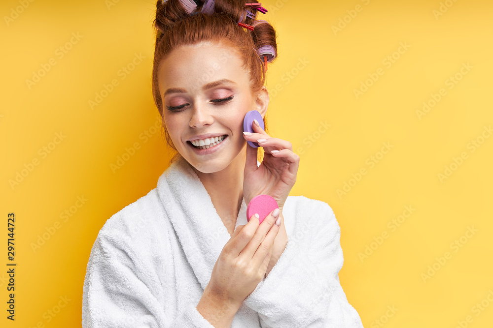Fototapety, obrazy: Careful beautiful woman isolated over yellow background, holding beauty sponges near face. Attractive redhead woman in bathrobe. with curlers