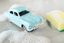 Car Wash Scene With Small Mass Production Toy Model Of Soviet Popular Vintage Car Volga GAZ-21, Yellow Sponge, Foam Around  On Grey Background.