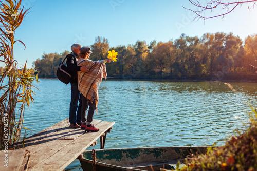 Senior family couple walking by autumn lake Fototapet