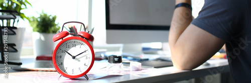 Red alarm clock stand at worktable with thoughtful man Canvas Print