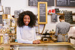canvas print picture - Smiling young African American entrepreneur working behind her cafe counter